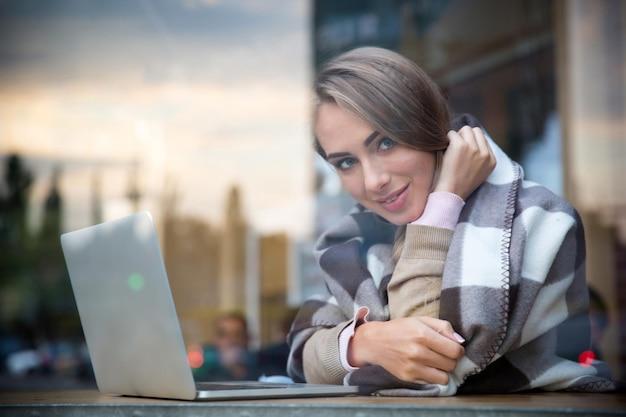 Retrato de uma menina sorridente sentada com um laptop em um café