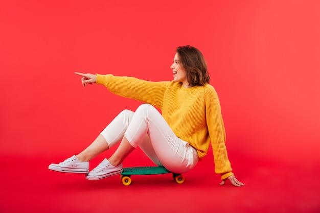 Retrato de uma menina sorridente, sentado em um skate