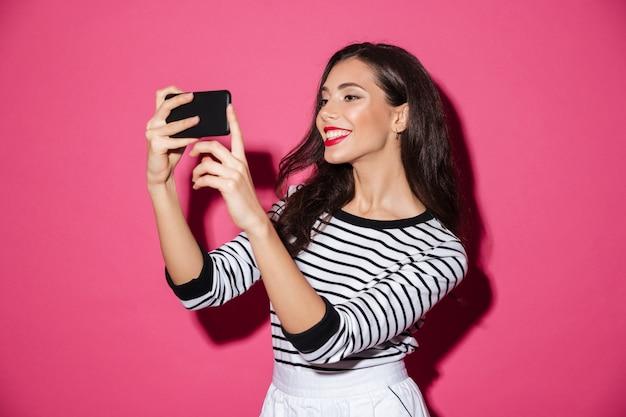 Retrato de uma menina sorridente tomando uma selfie