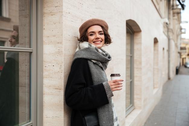 Retrato de uma menina sorridente, vestida com roupas de outono