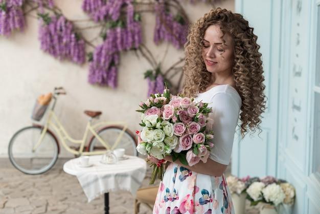 Retrato de uma menina suavemente encaracolada abraça um buquê de rosas em pé