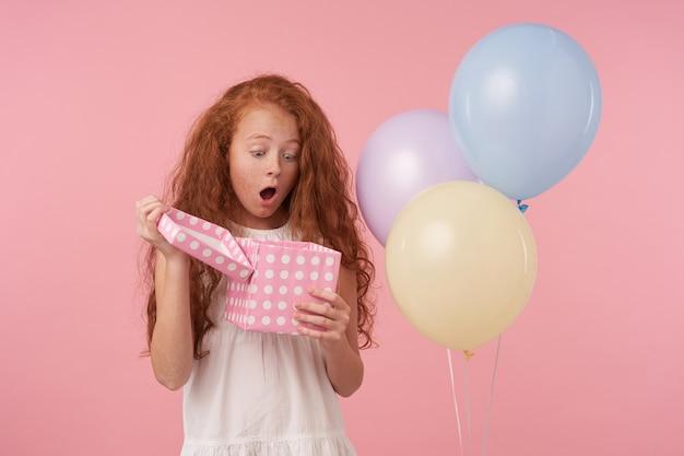 Retrato de uma menina surpresa com longos cabelos sedosos lixando sobre um fundo rosa de estúdio em roupas festivas, segurando a caixa de presente descompactada nas mãos e olhando para dentro com alegria