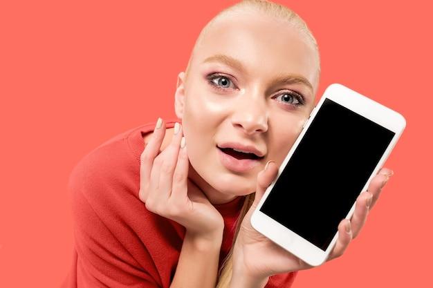 Retrato de uma menina surpresa, sorridente, feliz e atônita, mostrando o celular de tela em branco isolado sobre o fundo coral.