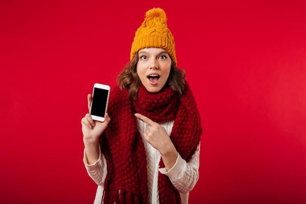 Retrato de uma menina surpresa, vestido com chapéu de inverno