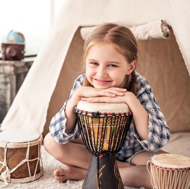 Retrato de uma menina tocando bateria tradicional africana djembe sentada na cabana no quarto das crianças