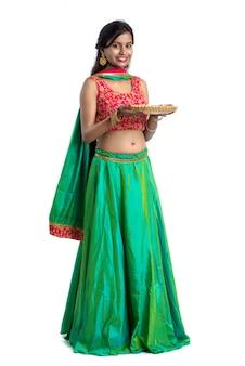 Retrato de uma menina tradicional indiana segurando diya, garota comemorando diwali ou deepavali com segurando a lâmpada de óleo durante o festival de luz na superfície branca