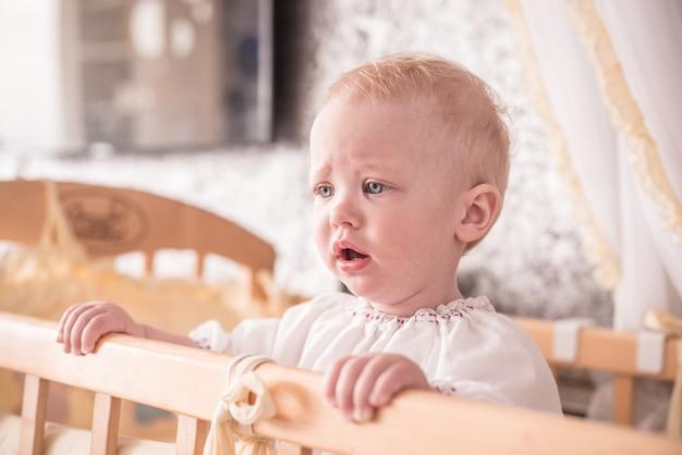 Retrato de uma menina triste com cabelos loiros e olhos azuis em casa em seu berço