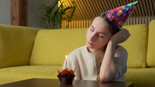 Retrato de uma menina triste com um pedaço de bolo com uma vela, a menina apaga a vela
