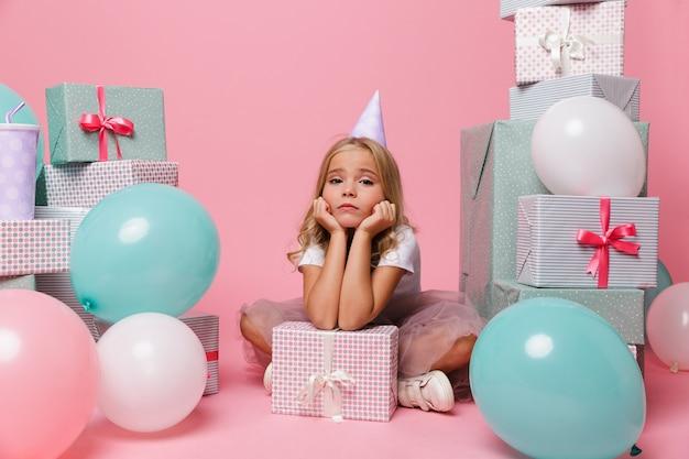 Retrato de uma menina triste em um chapéu de aniversário