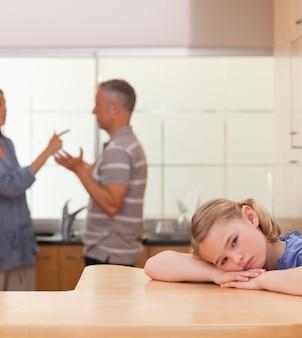Retrato de uma menina triste ouvindo seus pais discutindo
