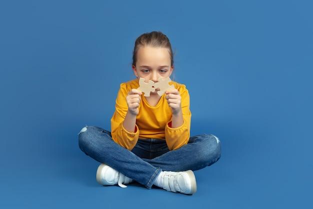 Retrato de uma menina triste sentada isolada no fundo azul do estúdio. como é ser autista. problemas modernos, nova visão das questões sociais. conceito de autismo, infância, saúde, medicina.