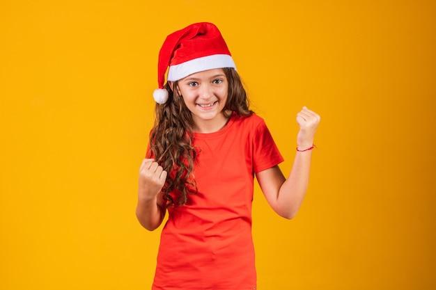 Retrato de uma menina vestida com roupa de natal, comemorando a vitória. sim!