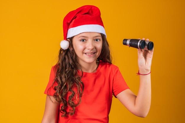 Retrato de uma menina vestida com roupa de natal, olhando através de um binóculo.