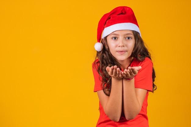Retrato de uma menina vestida com roupas de natal, soprando algo nas mãos.