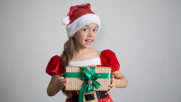 Retrato de uma menina vestida com uma fantasia de natal com um presente.