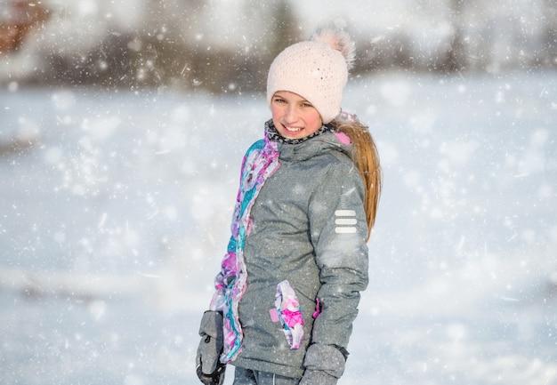 Retrato de uma menina vestida de esqui quente em tempo nevado ao ar livre