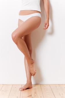 Retrato de uma metade do corpo feminino esbelto em roupa interior