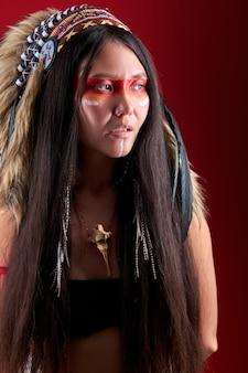 Retrato de uma misteriosa mulher xamânica indiana com penas indianas e maquiagem colorida olhando para o lado, isolado sobre a parede vermelha