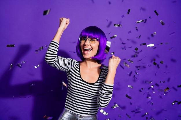 Retrato de uma moça bonita animada levantando os punhos gritando sim, isolado sobre um fundo violeta roxo