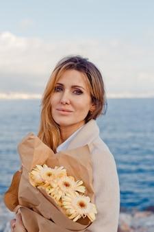 Retrato de uma moça bonita com flores em pé na beira-mar durante a tarde.