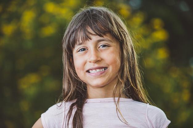 Retrato de uma moça bonita de sorriso na exploração agrícola. menina na fazenda em dia de verão. atividade de jardinagem. garota brasileira.