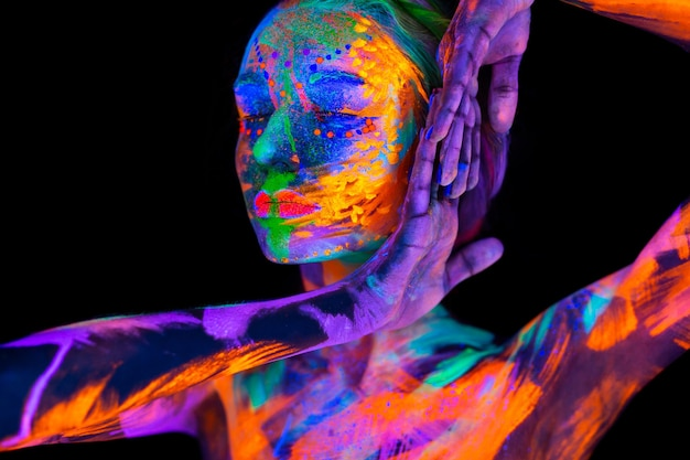 Retrato de uma modelo com maquiagem fluorescente posando em luz ultravioleta com maquiagem colorida