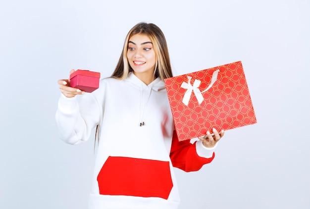 Retrato de uma modelo de mulher simpática de pé e segurando uma sacola com uma pequena caixa