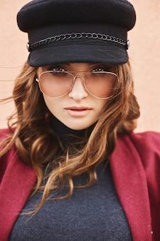 Retrato de uma modelo linda e elegante mulher de boné e óculos escuros.