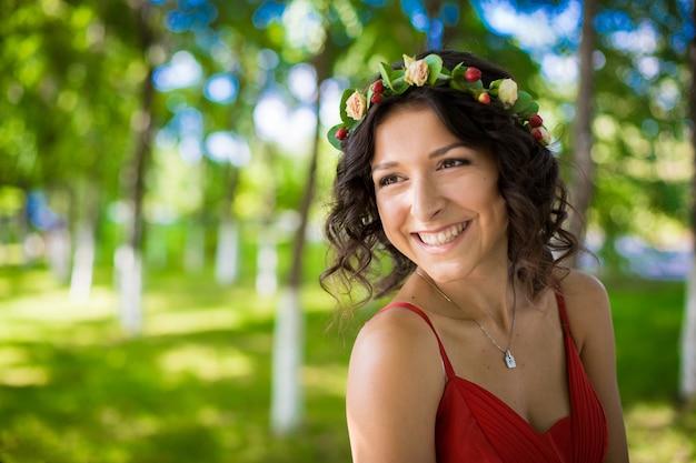 Retrato de uma morena com flores no cabelo em um parque verde.