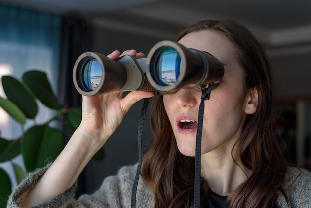 Retrato de uma morena surpresa com binóculos, olhando pela janela, espionando vizinhos