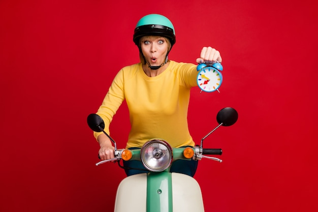 Retrato de uma motociclista louca e surpresa que anda de moto segurando o relógio