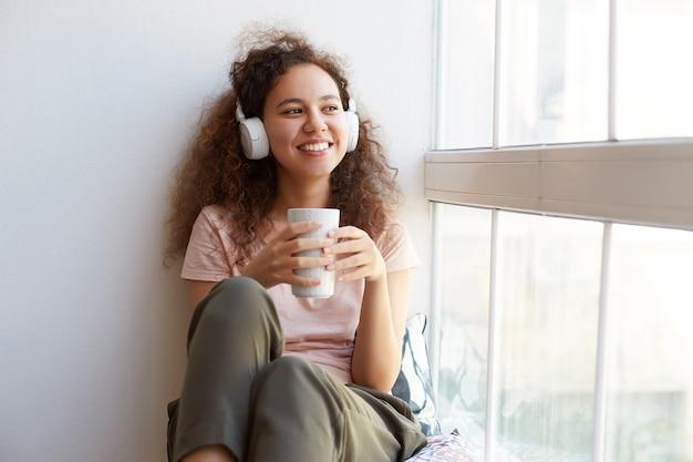 Retrato de uma mulata encaracolada jovem feliz sentada perto da janela, bebendo chá, ouvindo música favorita em fones de ouvido, olha para a janela e aproveitando o dia de sol em casa.