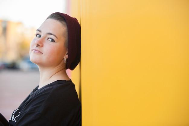 Retrato de uma mulher adolescente gay em uma parede amarela