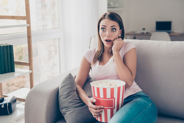 Retrato de uma mulher adorável assistindo tv com uma caixa de milho grande