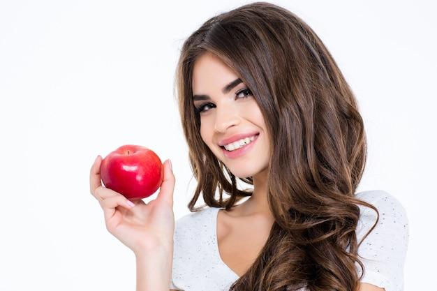 Retrato de uma mulher adorável e feliz com cabelo comprido, segurando uma maçã isolada em uma parede branca