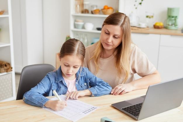 Retrato de uma mulher adulta carinhosa, ajudando a menina a fazer o dever de casa ou a estudar em casa enquanto está sentada à secretária, num interior acolhedor