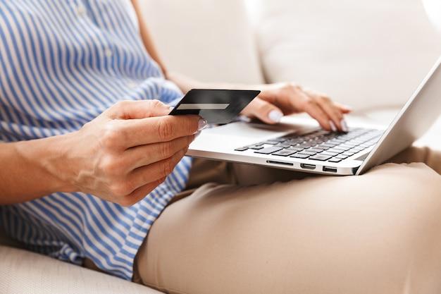 Retrato de uma mulher adulta com roupas elegantes, usando laptop e cartão de crédito, enquanto está sentada no sofá em um apartamento bem iluminado