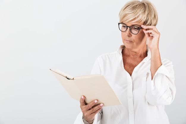 Retrato de uma mulher adulta concentrada usando óculos, lendo um livro isolado sobre uma parede branca em estúdio