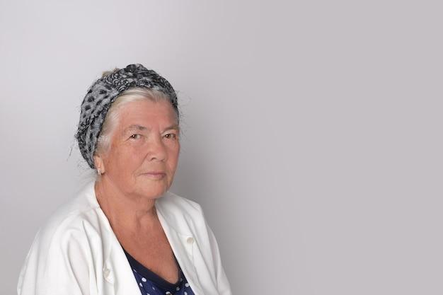 Retrato de uma mulher adulta de cabelos grisalhos atraente e fofa contra um fundo cinza com espaço de cópia