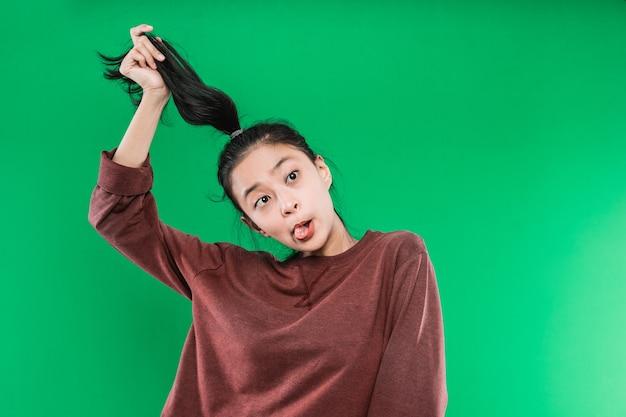 Retrato de uma mulher adulta de expressão engraçada e louca e a língua sai da boca enquanto segura seus longos cabelos negros isolados na parede verde