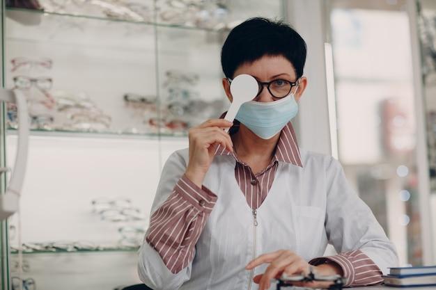 Retrato de uma mulher adulta de meia idade optometrista oftalmologista usando máscara protetora médica.