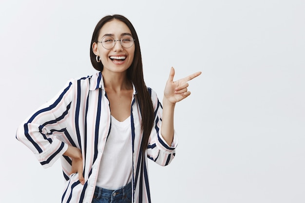 Retrato de uma mulher adulta feliz e despreocupada de sucesso em uma blusa estilosa sobre camiseta e óculos, rindo alegremente
