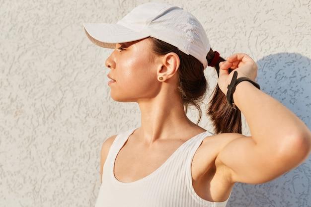 Retrato de uma mulher adulta jovem e desportiva com um top branco elegante e uma viseira posando contra uma parede cinza