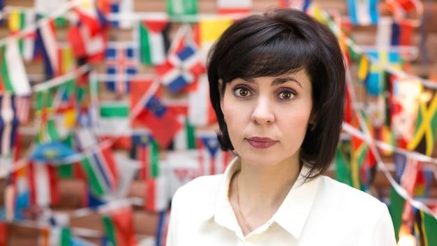 Retrato de uma mulher adulta no contexto de uma parede feita de bandeiras do mundo.