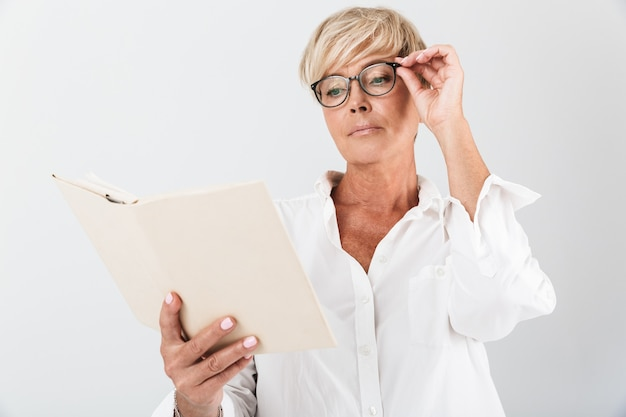 Retrato de uma mulher adulta séria usando óculos, lendo um livro isolado sobre uma parede branca em estúdio