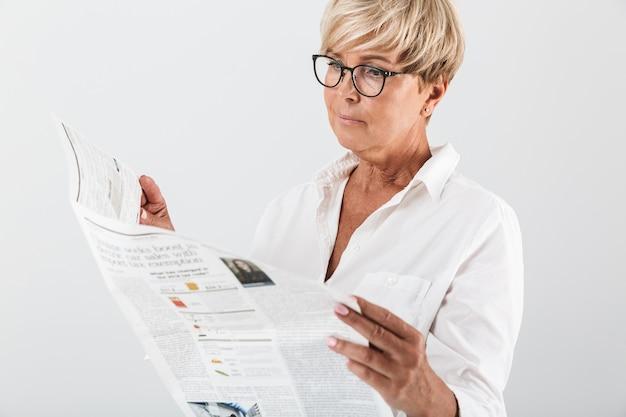 Retrato de uma mulher adulta usando óculos, lendo jornal isolado sobre uma parede branca em estúdio