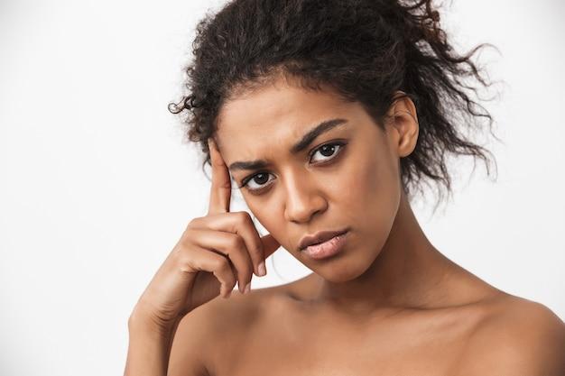 Retrato de uma mulher africana jovem cansada muito séria posando isolado sobre uma parede branca.