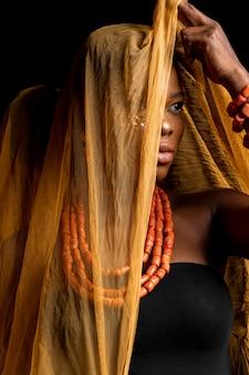Retrato de uma mulher africana usando acessórios tradicionais e véu amarelo