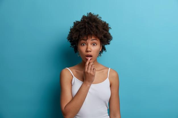 Retrato de uma mulher afro-americana admirada de choque, ouve notícias incríveis e surpreendentes, descobre uma relevância surpreendente, ouviu boatos ou más notícias, usa colete branco, isolado na parede azul