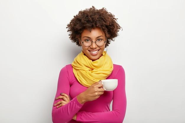 Retrato de uma mulher afro-americana alegre com uma expressão alegre, usa óculos ópticos, segura uma caneca de bebida, usa óculos ópticos, gola alta rosa e lenço, isolado sobre fundo branco
